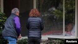 22일 미국 워싱턴주 커클랜드에 있는 요양센터 '라이프케어 센터'에서 코로나19 확진자가 창문 너머로 가족과 인사하고 있다.
