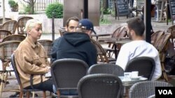 Young people having coffee in Paris. France reopened bars and restaurants mid-may as coronavirus cases dropped. (Lisa Bryant/VOA)