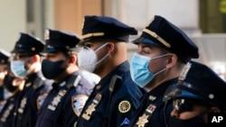 Polisi New York mengenakan masker di Gereja Katedral St. Patrick mengikut ibadah untuk menghormati 46 rekan polisi yang meninggal karena COVID-19, 5 Oktober 2020.
