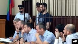 In this photo taken on Sunday, June 16, 2019, Abdulmumin Gadzhiev, the religious affairs editor of the independent weekly Chernovik, stands in a cage in a court room in Makhachkala, the Caspian Sea province of Dagestan, Russia, Sunday, June 16, 2019…