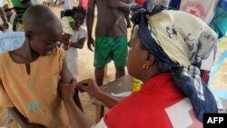 Un agent de la Croix-Rouge vaccine un enfant dans la localité de Nangungue (Est), au Cameroun, le 12 avril 2013. (AFP)