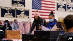 Women cast their ballots at a polling station in Windham, New Hampshire, Nov. 3, 2020.