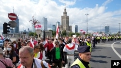 People carry banners of protest as they gather to denounce the regime of Belarusian President Alexander Lukashenko in Warsaw, Poland, Aug. 8, 2021.