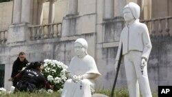 Deux femmes déposant des fleurs près des statues de Jacinta et Francisco, sanctuaire de Fatima, Portugal, le 11 mai 2017. (AP Photo/Armando Franca)