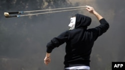 Một người biểu tình Palestine ném đá về phía cảnh sát Israel gần nhà tù quân sự Ofer của Israel tại thị trấn Betunia ở Bờ Tây trong những vụ đụng độ.