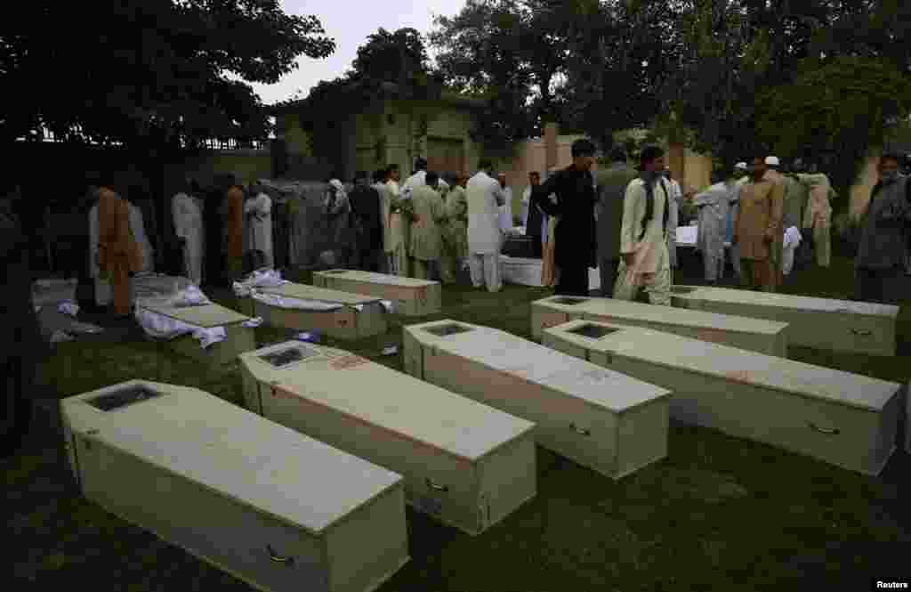 Mourners gather near the caskets of victims killed in a suicide bomb attack before funeral ceremony at a police headquarters in Quetta, Pakistan, August 8, 2013.