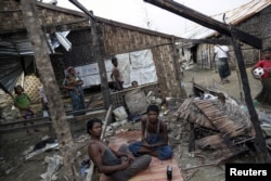 FILE - Rohingya people pass their time in a damaged shelter in Rohingya IDP camp outside Sittwe, Rakhine state on August 4, 2015