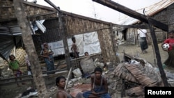FILE - Rohingya people pass their time in a damaged shelter in a Rohingya displaced-persons camp outside Sittwe, Rakhine state, Myanmar, Aug. 4, 2015