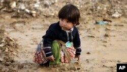 Anak pengungsi Suriah bermain lumpur di kota Al-Faour, Lebanon timur, dekat perbatasan dengan Suriah (2/12). (AP/Hussein Malla)