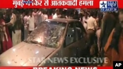In this image from Indian television channel Star TV, Indian bystanders and security personnel gather around the wreckage of a vehicle after a suspected bomb blast in Mumbai, July 13, 2011