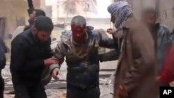 Сирийцы помогают раненному мужчине после авиаудара по пригороду Дамаска Масраба. Сирия. 1 января 2018 г.