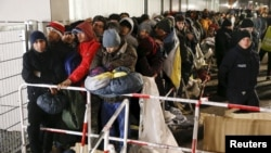 FILE - Migrants queue on a street to enter the compound outside the Berlin Office of Health and Social Affairs (LAGESO) for their registration process in Berlin, Germany, Dec. 9, 2015.