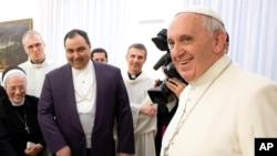 FILE - In this photo provided by the Vatican newspaper, Pope Francis smiles during an event at the Vatican on Jan.21, 2014.