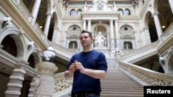 FILE - Austrian data activist Max Schrems stands in the courthouse after his trial against Facebook in Vienna, April 9, 2015.