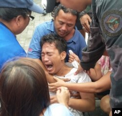 Police and rescuers comfort a crying passenger after he was brought ashore from a capsized passenger ferry July 2, 2015, in Ormoc city, central Philippines.