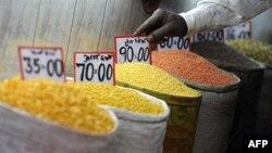 Nhân viên bán hàng sắp xếp bảng giá tại 1 khu chợ ở New Delhi