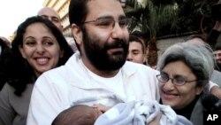 Alaa Abdel-Fattah, com o seu filho recém-nascido ao colo, Cairo, Egipto.