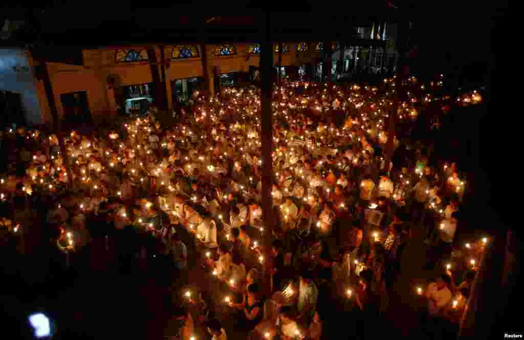 Participants hold candles during a mass prayer to call for justice in the trials of dissident blogger Nguyen Huu Vinh and land protection activist Can Thi Theu, at the Thai Ha Church in Hanoi, Vietnam, Sept. 18, 2016.