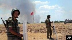 Tentara Turki berjaga-jaga di perbatasan dengan Suriah di Suruc, sementara asap terlihat di latar belakang dari Kobani.
