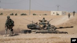 Turkish tanks and troops stationed near Syrian town of Manbij, Syria, Oct. 15, 2019. Russia moved to fill the void left by the United States in northern Syria on Tuesday, deploying troops to keep apart advancing Syrian government and Turkish forces.