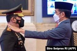 Presiden Joko Widodo (kanan) melantik Jenderal Listyo Sigit Prabowo (kiri) sebagai Kapolri baru di Istana Presiden Jakarta, 27 Januari 2021. (Foto: Biro Setpres/AFP)