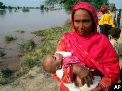 A mother carrying a child cries while evacuating her home along the flooded Chenab River, in Jhang, Pakistan, Sept. 10, 2014.
