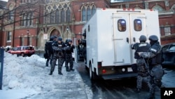 SWAT team officers arrive at a building at Harvard University in Cambridge Dec. 16, 2013.