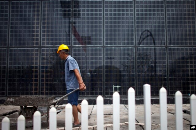 FILE - Solar panels at a factory in Baoding, in northern China's Hebei province. China, the world's largest polluter of climate changing emissions, is aggressively adopting solar energy to cut its dependence on fossil fuels.