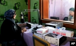 Zarghona Hassan, an activist and the founder of Radio Shaesta station prepares to go on-air, in Kunduz, Afghanistan, March 4, 2016.
