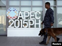 A military personnel walks past an APEC logo with his sniffer dog at the media center of the Asia-Pacific Economic Cooperation (APEC) summit in the capital city of Manila, Philippines November 17, 2015.