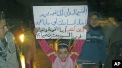 """A girl whose father was killed during the recent shelling on Baba Amr district protests against Syria's President Bashar al-Assad in Al Qusour, Homs, March 3, 2012. The placard reads """"The hypocritical international community wants to send aid to Baba Amr."""