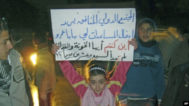 "A girl whose father was killed during the recent shelling on Baba Amr district protests against Syria's President Bashar al-Assad in Al Qusour, Homs, March 3, 2012. The placard reads ""The hypocritical international community wants to send aid to Baba Amr."