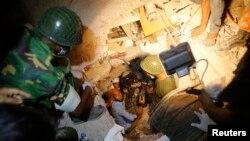 2013年4月26日救援人员在首都达卡郊外倒塌制衣厂的瓦砾中搜寻可能幸存的人。