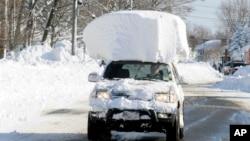 2014年11月19日纽约大雪后,兰开斯特20号公路上背着大雪块行驶的车辆。