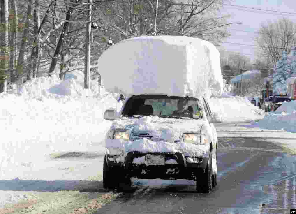 A vehicle, with a large chunk of snow on its top, drives along Route 20 after digging out after a massive snow fall in Lancaster, New York on Nov. 19, 2014. Another two to three feet of snow is expected in the area.