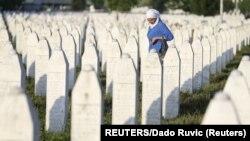 ARHIVA - Žena hoda između grobova u Potočarima, 11. jula 2017. (Foto: Reuters/Dado Ruvić)