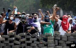 Protesters yell from behind the roadblock they erected as they face off with security forces near the University Politecnica de Nicaragua in Managua, Nicaragua, April 21, 2018.