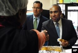 FILE - Deval Patrick, right, then Massachusetts' governor, shakes hands with bakery employees as then-Gov. Dannel P. Malloy, center, looks on, during a campaign stop, Oct. 10, 2014, in Hartford, Conn.