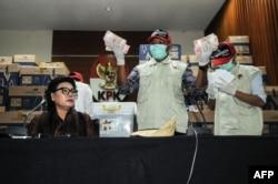Komisioner KPK Basaria Panjaitan bersama para pejabat KPK dengan bukti uang tunai yang disita dari anggota DPR yang ditetapkan sebagai tersangka korupsi, di Jakarta, 17 April 2019. (Foto: AFP)