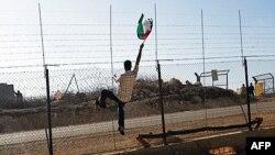 Một người biểu tình giơ cao lá cờ Palestine trước các binh sĩ Israel để phản đối rào chắn ở Bilin