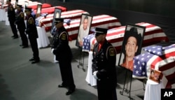 FILE - Honor guard stand in front of caskets prior to a memorial service for first responders who died in the fertilizer plant explosion in West, Texas, April 25, 2013, in Waco, Texas.