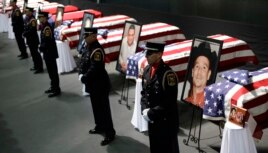 Honor guard stand in front of caskets prior to a memorial service for first responders who died in last week's fertilizer plant explosion in West, Texas, April 25, 2013.