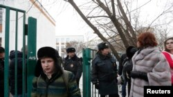 Interior Ministry members evacuate people after an armed student took hostages at a high school on the outskirts of Moscow, Feb. 3, 2014.