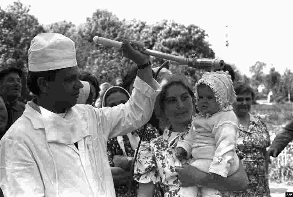 Советский техник проводит обследование ребенка на радиационное облучение, деревня Копылово, Киев, 9 мая, 1986г.