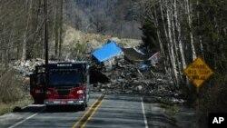 23일 미국 워싱턴주 오소시 인근에서 산사태로 무너져 내린 흙더미가 도로를 덮쳤다. 흙더미에 휩쓸려온 가옥도 보인다.