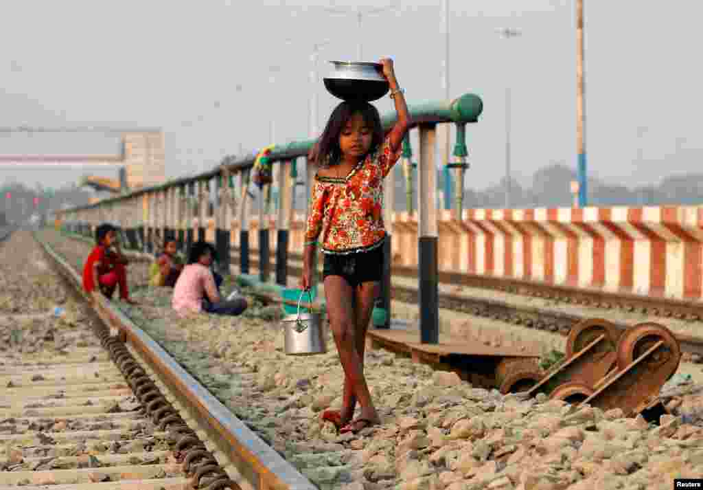 A girl carries water in a pot and a bucket on the outskirts of Agartala, India.