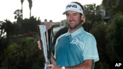 Bubba Watson poses with his trophy on the 18th green after winning the Genesis Open golf tournament at Riviera Country Club on Sunday, Feb. 18, 2018, in the Pacific Palisades area of Los Angeles.