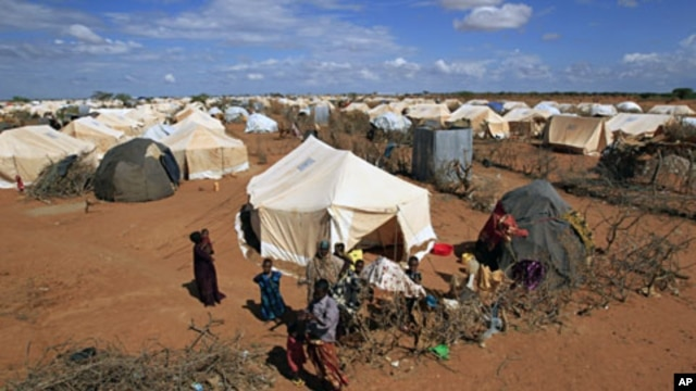 Refugees stand outside their tent at the Ifo Extension refugee camp in Dadaab, near the Kenya-Somalia border (File)