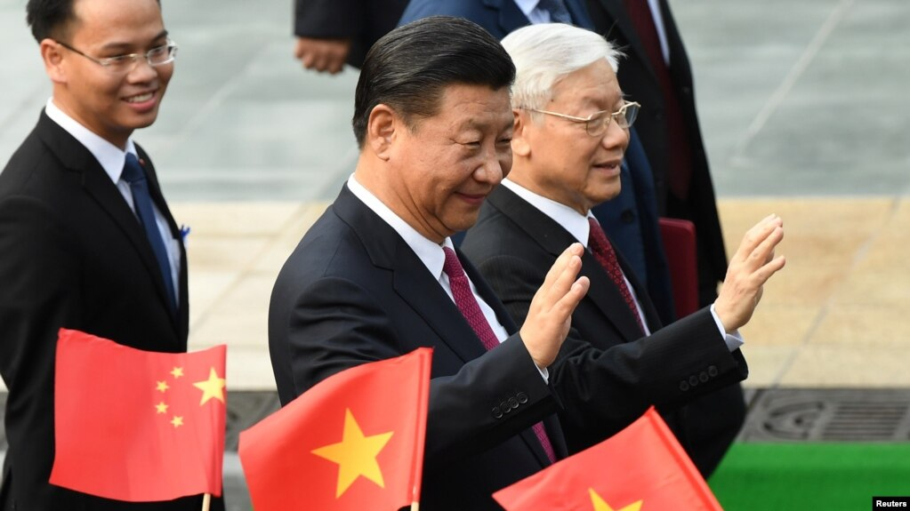 Chủ tịch Trung Quốc Tập Cận Bình và TBT Đảng CSVN Nguyễn Phú Trọng vẫy tay chào các em học sinh cầm cờ hai nước tại lễ đón mùng ông Tập tới thăm Hà Nội hôm 12/11/2017. Ảnh REUTERS/ Hoang Dinh Nam
