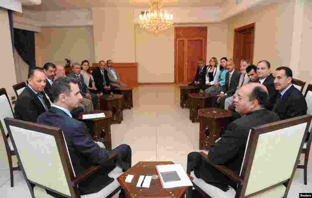 Syria's President Bashar al-Assad (L) speaks with Shukri Bin Suleiman Harmasi (R), secretary general of the Tunisian Immutable Principles Party, during a meeting in Damascus, May 23, 2013.